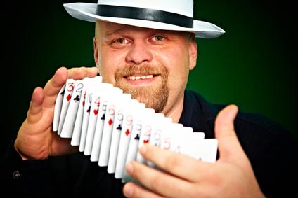man skilfully shuffles playing cards